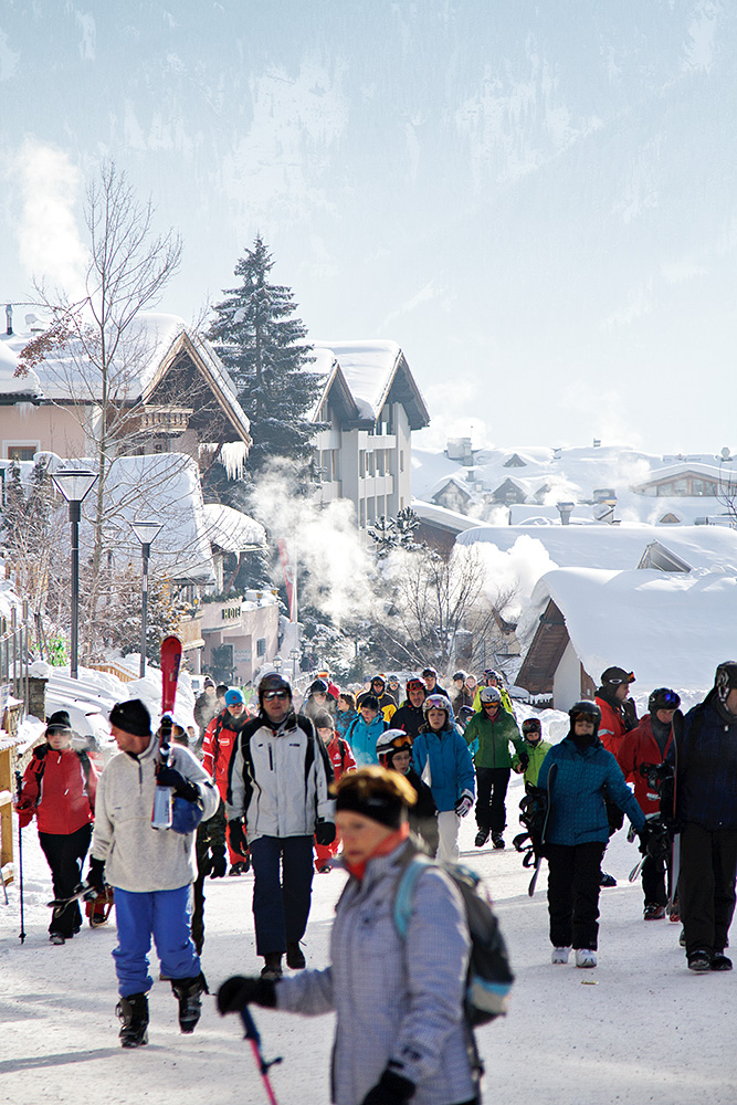 Serfauksen kylän pääkatu täyttyy aamulla hissin ala-asemaa kohti kävelevistä hiihtäjistä. Kadun alapuolella kulkee ilmainen vaihtoehto kävelysiirtymälle, kylän halki ala-aseman ja parkkipaikan väliä suhaava hiihtometro.
