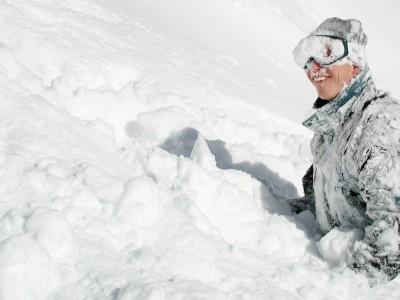 Pieni kalliodroppi, pari kärrynpyörää pehmeässä lumessa ja hymyillen välineitä etsimään.
