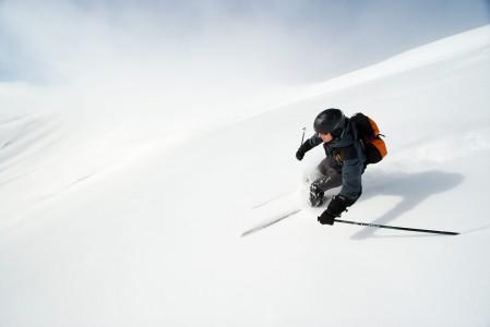 Pilvi ja laskija vaeltavat vastakkaisin suuntiin. Laskija suuntaa kohti Finkenbergin ala-asemaa Mayrhofenissa, kun taustalla pilvi karkaa laaksosta taivasta kohti.