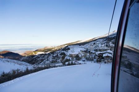 Sierra Nevadan hiihtokeskuksen majoituskeskittymä kutistuu takana vauhdilla gondolin lähtiessä nousemaan kohti aamuauringossa odottelevaa väliasemaa.