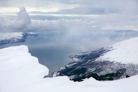 Storhaugen-huipun petollisen kauniit maisemat Lyngenistä. Lumilippaa on syytä varoa, sillä lipan sortuessa reunalta on pudottu kohtalokkaasti 200 metriä.