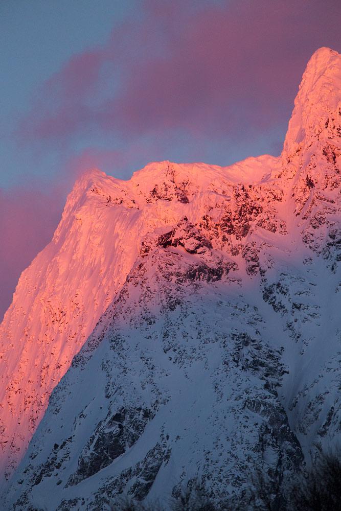 Päivän viimeiset valonsäteet osuvat Lyngenin korkeimmille huipuille ennen sinistä hetkeä ja illan tummumista.
