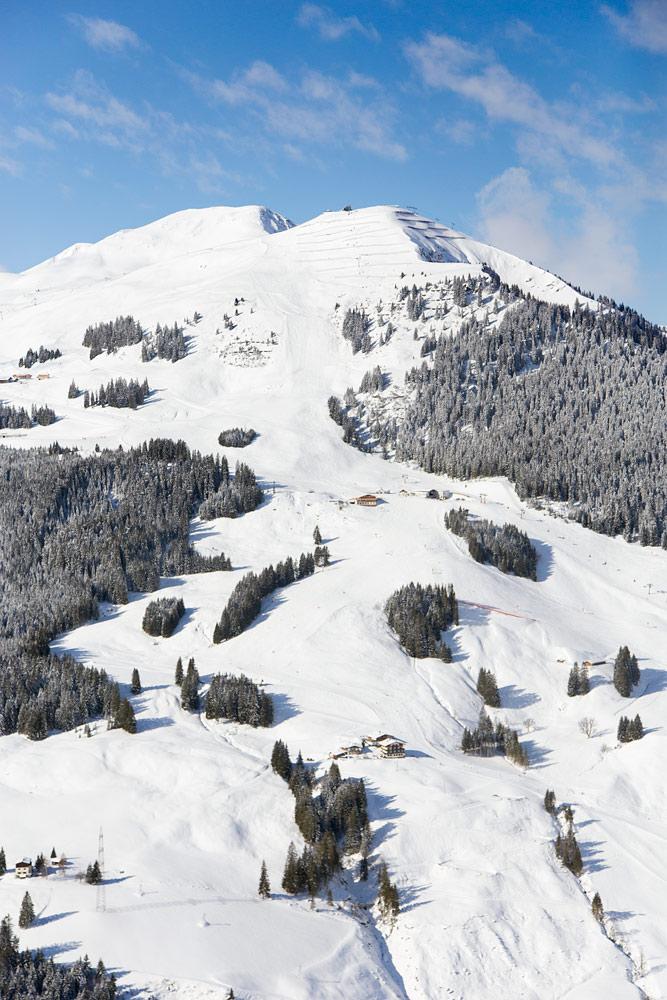 Saalbachin Zwölferkogelin mukavaprofiiliset rinteet ja tunnelmalliset rinneravintolat vastapäiseltä Schattbergin hiihtoalueelta katsottuna.