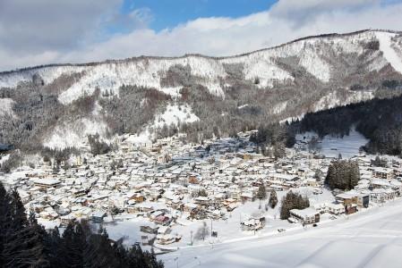 Nozawa Onsenin tiiviisti rakennettu kylpyläkylä on aivan rinteiden juurella. Rinteille noustaan kuvan oikeasta laidasta.