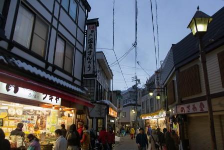 Nozawa Onsenin tunnelmallisessa kylässä kapeat lämmitetyt kadut risteilevät mäen alarinteellä.