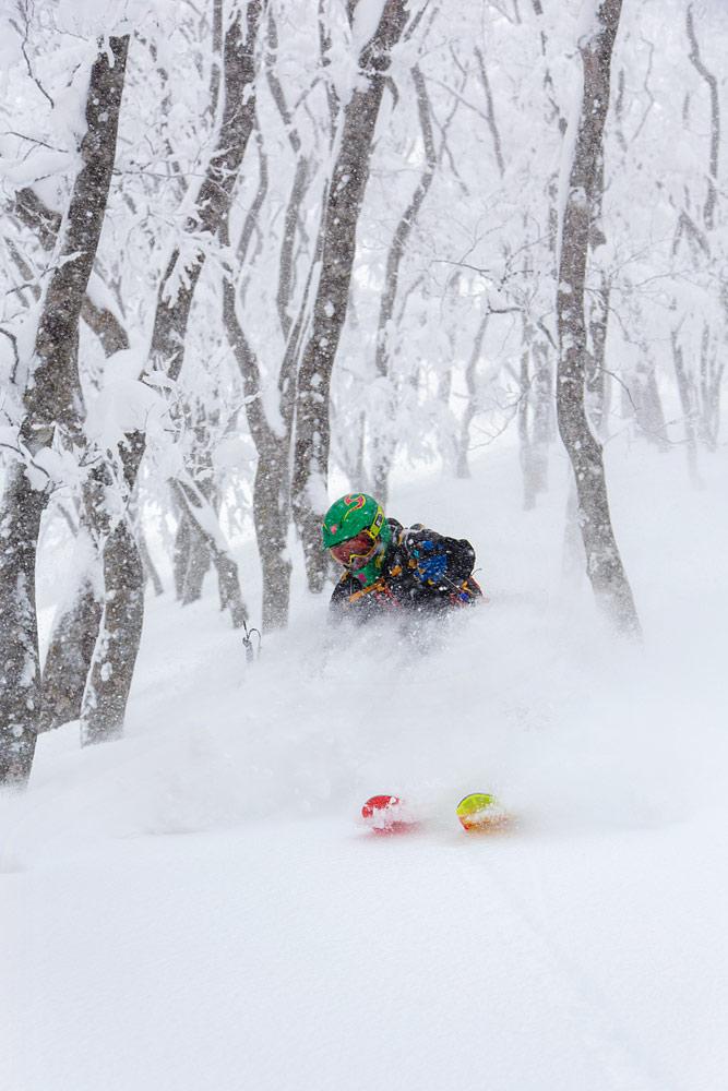 Suohirviömäinen vihreä kypärä etenee uhkaavasti Nozawa Onsenin metsissä lumipöllyn saattelemana.