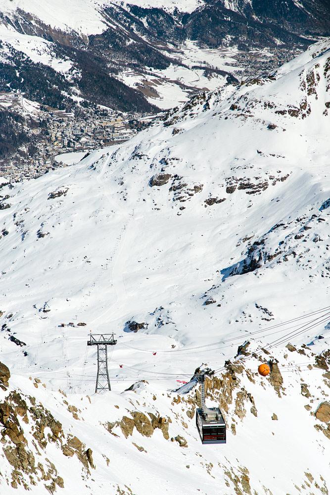 Takana näkyvästä St. Moritzin kylästä tarvitaan ensin auto- tai bussisiirtymä Corvatsch -hiihtoalueen ala-asemalle ja sieltä kaksiosainen kabiininousu tänne. Ylhäällä kannattaa sijoittaa hetki laskuaikaa maisemien ihailuun.