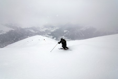 Davosin Jakobshorn-hiihtoalueen reunimmainen rinne kulkee harjanteena suoraan kaupunkia kohti. Vastapäinen Parsenn jää lumipilven taakse.