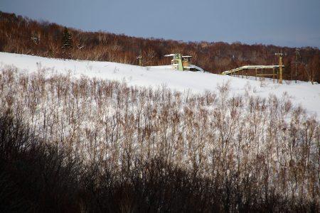 Iwanai Resortin maisemassa on vielä aikoinaan vuorella toimineen hiihtokeskuksen rapistuneet hissit ja rakennukset.