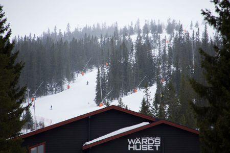 Sälenin Lindvallen-hiihtoalueen punaiset Lisa ja Lotta -rinteet näkyvät tunnelmallisen Wärdshuset -rinneravintolan takaa.